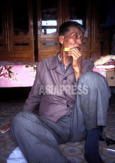 飢餓のため、わずか8時間前に北朝鮮から脱出して来たばかりの老人。「今の朝鮮は倭政(日本統治)よりひどい。老人が真っ先に死んだ」。取材中ずっと食べ物を口に運び続けた。1997年7月中国吉林省にて撮影石丸次郎(アジアプレス)