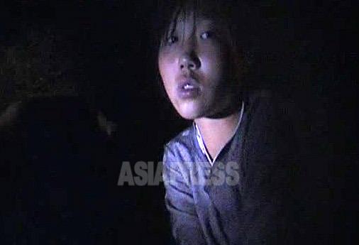 真っ暗闇の道路脇に座って石炭を袋詰めしていた中学生の少女。近くの作業場から失敬してきたものだという。売って生活の足しにすると言った。2009年8月平安南道にて撮影キム・ドンチョル(アジアプレス)