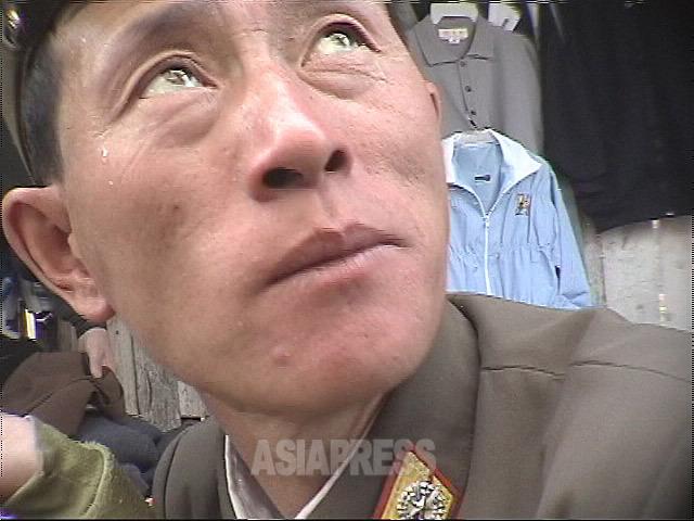 子供連れで市場に来ていた将校。職業軍人だが、家族分の配給が度々途絶し、妻が商売をして生計を維持するのが当たり前になっている。2003年9月恵山市にて撮影アン・チョル(アジアプレス)