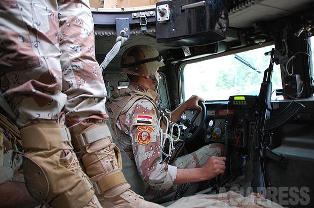 イラク軍車両に乗り込む。米国製ハンヴィーは防弾防爆装甲強化タイプだが、それでも武装組織の路肩爆弾で吹き飛ばされる被害があいついでいた。左は機銃兵の足。ルーフ部分で機銃を構え警戒する。(2010年・モスル:撮影・玉本英子)