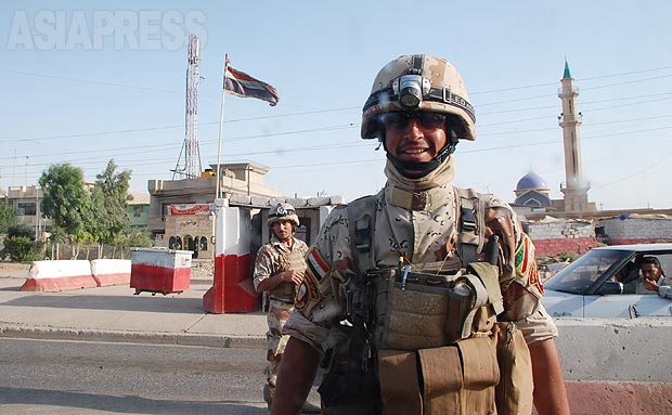 モスル市内の検問所で警備にあたるイラク兵。検問所はとくに自爆車両の攻撃や遠方からの狙撃で狙われた。警察にも武装組織の協力者がいたり、偽装警官が自爆することもあるため、警察車両でさえ信用していなかった。(2010年・モスル:撮影・玉本英子)