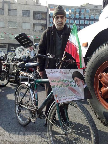 イランの革命記念日で、最高指導者のポスターを自転車に取り付けていた男性(撮影筆者/2010年)