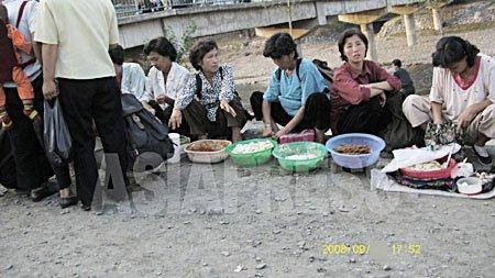노상에서 집에서 만든 빵과 떡을 파는 평양시 강동군의 여성들. 식량배급도 노임도 전혀 나오지 않기 때문에 이러한 장사로 생계를 유지하고 있다. 2008년9월 촬영 장정길(아시아프레스)