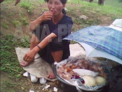 길에서 꽈배기와 떡을 파는 여성. (2010년6월 평안남도 김동철 촬영)