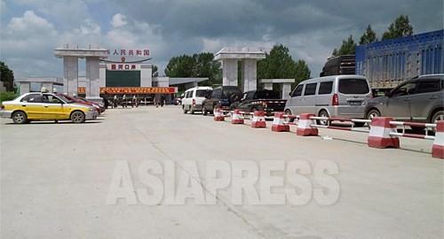 라선시를 목적지로 하는 수십대의 차량이 통관을 기다리고 있다. 이곳에서부터 라진항까지는 50킬로미터 정도다. 좌측에 북한에서의 방문자와 귀국자를 기다리는 택시도 보인다. 7월 6일 중국 길림성 훈춘시의 권하세관. 촬영 박영민 (아시아프레스)