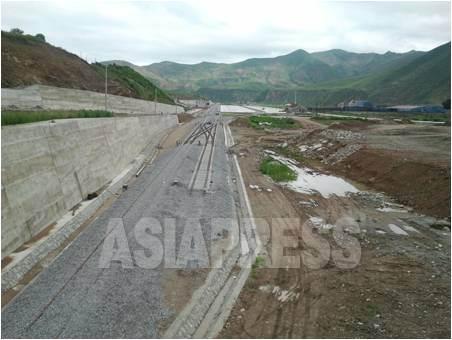 중국의 길림성 연변조선족자치주에 건설되고 있는 '화평철도'. 멀리 보이는 흰색 바닥이 남평진 역사 앞마당이다. 뒤로 보이는 산은 북한 지역이다. 2012년 7월 5일 박영민 촬영(아시아프레스)