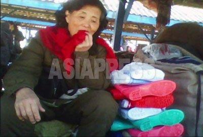 평안남도에 있는 장마당에서 한 여성이 구두를 팔고 있다. 90년대 이후 북한 주민에 있어서 장사는 유일한 현금 수입원이다. 2010년 10월 김동철 촬영 (아시아프레스)