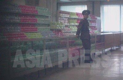 진열용의 생리용품, 북한의 상점은 대개 카운터의 뒤편으로 상품이 진열돼 손님이 만질 수 없다. 서있는 사람은 보안원(경찰) (사진은 모두 2011년 9월 구광호 촬영)