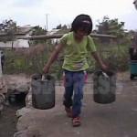 커다란 물동이를 옮기는 소녀. 농촌에서는 전력난으로 수도가 나오지 않는 지역이 늘어나, 우물을 길어 생활하는 것이 일상적인 광경이 됐다. (2008년 10월 황해남도 과일군 심의천 촬영)