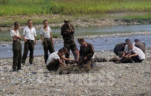 (참고사진) 강동군의 일반 부대 병사들. 야윈 모습이다. 주변의 밭에서 훔친 옥수수를 굽고 있다. 군대의 식량 부족은 이 20년간 만성화 되고 있다. 2008년 9월 장정길 촬영 (아시아프레스)