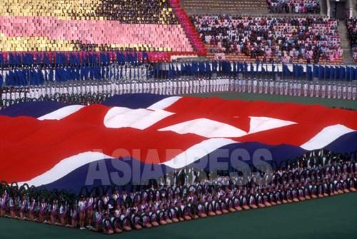 국기가 등장한 집단체조 공연, 시종일관 지도자에 대한 업적 칭송이 <아리랑> 공연의 요점이다. 사진은 <아리랑>이라 칭하기 전 1995년의 집단체조. 촬영 이시마루 지로.
