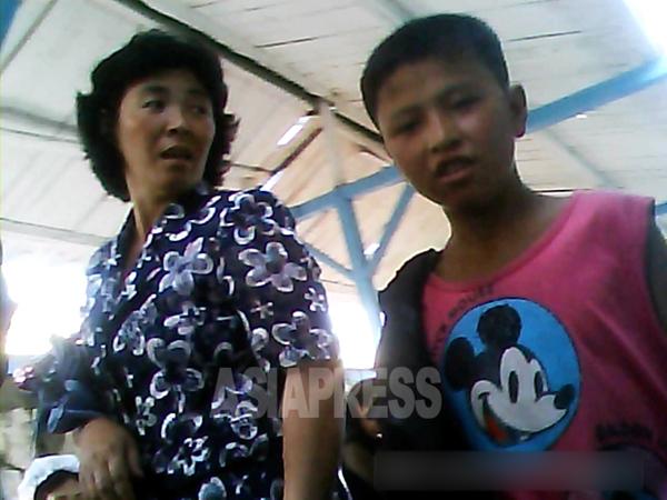 모자간으로 보이는 두 사람. 소년이 입은 셔츠에 미키마우스 그림이 보인다