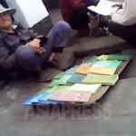 늙은 남성이 시장 바닥에 앉아 책을 팔고 있다