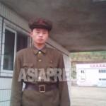'노농적위대' 복장을 한 남성이 기업소 출입을 통제하기 위해 경비를 서고 있다.