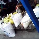 많은 쌀자루를 진열해 놓고 손님을 기다리는 여성 장사꾼. 맨 오른쪽 쌀자루에는 '4900'(원)이라고 적힌 가격표가 보인다.