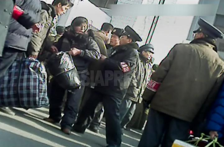 평안북도 신의주시에서 '질서유지대'라는 완장을 찬 철도원이 큰 짐을 든 사람이 역내로 들어가지 못하도록 단속하고 있다. 2012년 11월 북한 내부 취재협력자 촬영(아시아프레스)