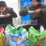 식사를 하는 상인들 앞에 중국산 쌀이 늘어서 있다. 가격을 물으면 중국돈으로 대답한다. 2013년 10월 촬영 (아시아프레스)