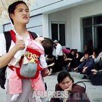 아기띠로 아이를 안은 여성. 5년 정도 전까지는 등에 업는 것이 일반적이었다. 중국산이라고 한다. 수입품을 통해 외국 문화나 정보가 국내에 유입된다. 2011년 6월 평양시 중구역에서 구광호 촬영(아시아프레스)