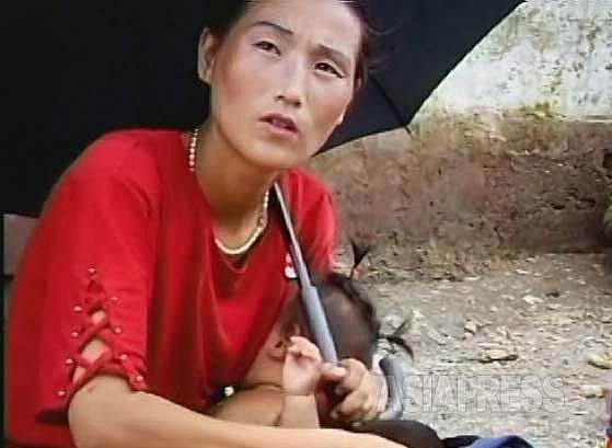 젖먹이를 데리고 노상에서 떡이나 빵을 파는 여성. 양산에 화장은 잊지 않는다. 2007년 7월 황해북도 사리원시에서 촬영(아시아프레스)