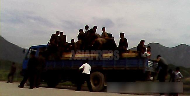 """삼수발전소 바로 옆에 위치한 검문소에서 승객들이 증명서 검열을 받기 위해 트럭의 짐칸에서 내리고 있다. 2013년 8월 양강도에서 촬영 """"민들레""""(아시아프레스)"""