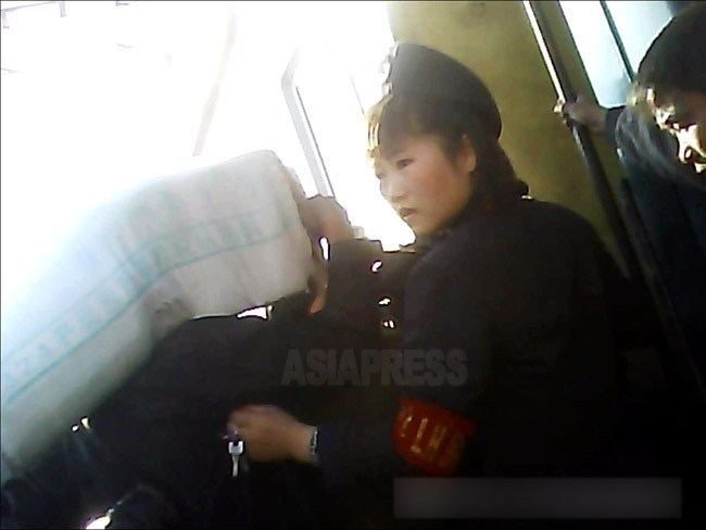 큰 짐을 지고 열차에 탑승하려는 승객을 규제하는 여성 열차 안내원(차장). 베레모를 쓰고 있다. 2013년 10월 양강도 혜산 역에서 촬영 '민들레'(아시아프레스)