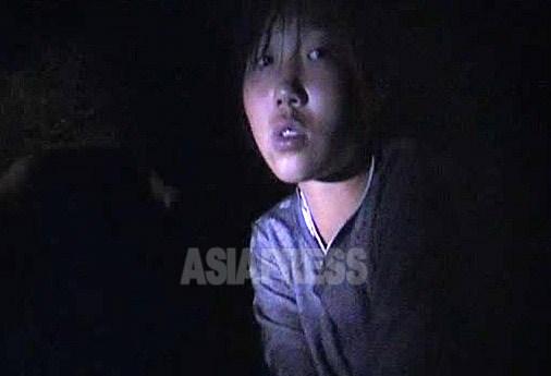 깜깜한 밤 도로변에 앉아 석탄을 주머니에 넣고 있던 중학생 소녀. 가까운 작업장에서 슬쩍 가져왔다고 한다. 팔아 생활에 보태려 한다고 말했다. 2009년 8월 평안남도에서 촬영 김동철(아시아프레스)