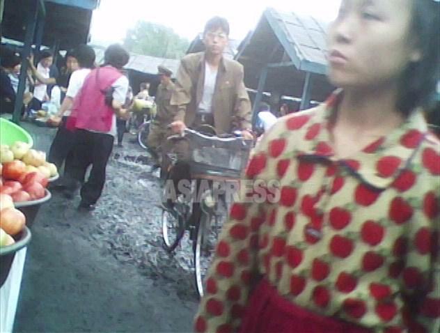 사과 무늬가 그려진 더러운 셔츠에 트레이닝 팬츠를 입은 소녀가 시장을 맴돌고 있다. 시선은 계속 노점의 음식을 향하고 있다. 2010년 6월 평안남도에서 촬영(아시아프레스)