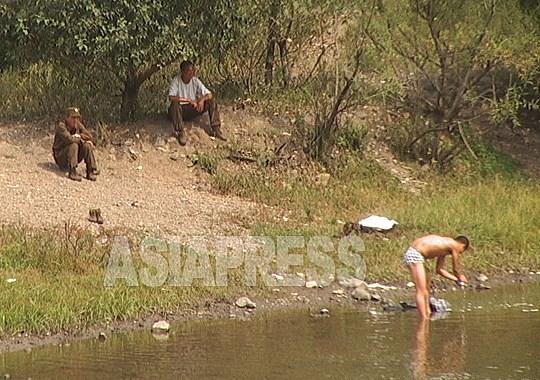 찌는 더위 속에 강에서 한가롭게 목욕, 세탁하는 국경 경비병들. 2003년 9월 두만강 상류의 중국 측에서 촬영 이시마루 지로(아시아프레스)