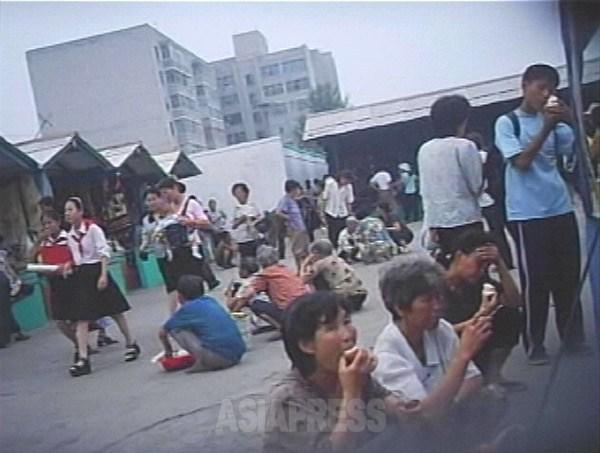 빨간 넥타이를 맨 여중생(왼쪽)은 통굽 샌들을 신고 있다. 주저앉은 여성들이 먹고 있는 것은 아이스. 2007년 8월 하순 평양시 선교 시장에서 촬영 리 준(아시아프레스)