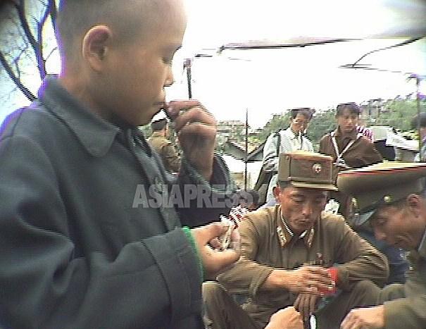 술을 마시는 장교의 옆에서 부랑아가 음식을 주워 먹고 있다. 1998년 10월 강원도 원산시에서 촬영 안 철(아시아프레스)