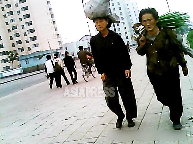 큰길로 짐을 나르는 할머니들. 시장에 가는 것일까, 귀로에 오른 것일까. 그래도 훌륭한 파다. 2013년 9월 평안남도 평성시에서 촬영 아시아프레스
