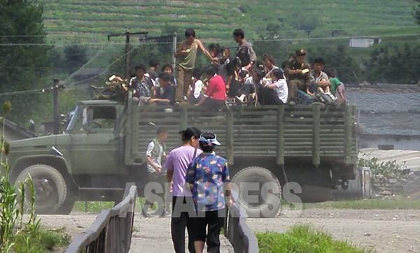 군용 트럭의 짐칸에 사람이 가득 타고 있다. 기름값이나 부품 대금을 벌기 위해 군부대가 직접 '써비차'를 운영하는 경우도 있다. 2008년 9월 평양시 외곽에서 촬영 장정길(아시아프레스)