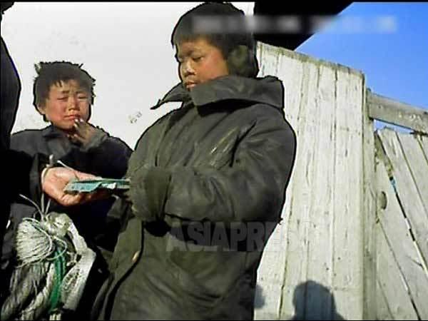 시장에서 한국 드라마 VCD(혹은DVD)를 파는 노숙자 아이들. 2013년 3월 평안남도 신의주시에서 촬영 아시아프레스