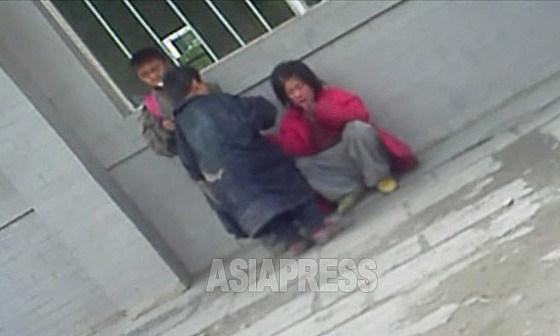 시장 근처를 배회하는 세 명의 꼬제비. 빨간색 윗옷을 입고 앉아있는 것은 여중생인가? 찢어진 어른용 옷을 걸친 아이도. 2012년 11월 양강도 혜산시에서 촬영 아시아프레스