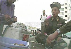 길에 주저앉은 병사가 먹는 것은 아이스 캔디. 냉장고를 소유한 부자가 만들어 '판매자'인 여성에 도매한다. 2008년 9월 황해남도 해주시에서 심의천 촬영(아시아프레스)