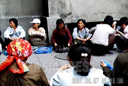 Women street vendors sitting in a line, selling goods in the area between apartment buildings. It is illegal to do this and the local authorities often made crackdowns and forcibly confiscated all goods and charged fines. But since the people's backlash was provoked, the team just patrols around and disperses them but confiscation measures are not taken these days. (Moranbong District, Pyongyang. June, 2011. Taken by Gu Gwang-ho) (C)ASIAPRESS
