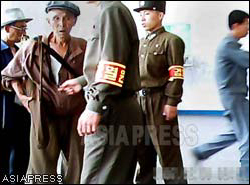 "An old man was stopped by soldiers. He got raked over for his shabby-looking clothes. The soldier's armband reads ""inspection"". (Taken by Gu Gwang-ho) (C) ASIAPRESS"