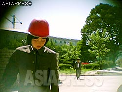 Numerous young students are mobilized to work at construction sites, but because they are unfamiliar with the work, more than a few are injured. This young woman wearing a helmet is a mobilized member of theYouth League Shock Troops which is usually deployed to the state -level construction projects.(Aug/2011/Taken by Gu Gwang-ho)