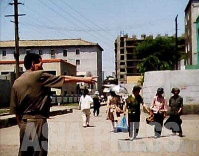 The authorities are zealous about cracking down on street side vendors. This photo shows a local municipality officer (left) driving street sellers away. In the central part of the city, they usually crack down on vendors on the main streets or near publicly-run markets, but during events that attract large numbers of foreign visitors safety officers (police) are called in to make sure no buying or selling is allowed at all even on the back streets.( June 2011, Moranbong District, By GU Gwang-ho) ASIAPRESS
