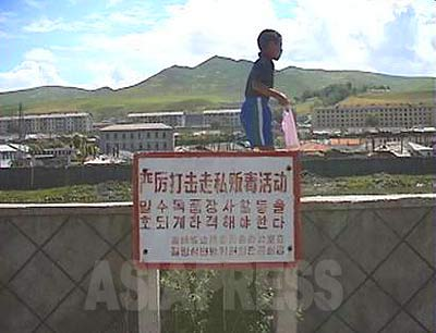 """A signboard put up in Changbai County, in a town on the Chinese border upstream on the Amrok-gang(Yalu River). The signboard says """"We must crack down firmly on trading of poison (drugs) and smuggling"""". Changbai County is across the river from Hyesan City, Ryanggang Province/North Korea, and is one of the most busy areas for smuggling. (1999 Jilin Province/China - Photo by ISHIMARU Jiro) ASIAPRESS"""