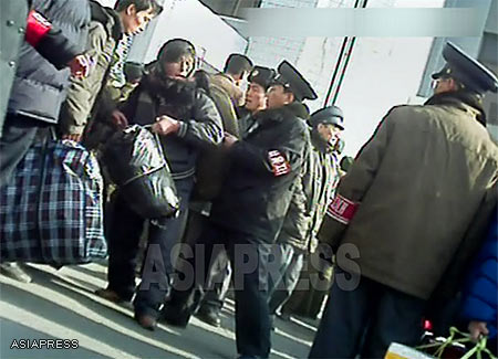 In front of the Sinuiju railway station people carrying large bags into the station are being stopped and searched by the officers of the Public Order Maintenance Corps (질서유지대), on the lookout for illicit materials being distributed within the country. Sinuiju City, North Pyongan Provice. ( November 2012, Taken by Rimjin-gang's reporting partner in North Korea) ASIAPRESS