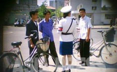 "These three men were stopped at an intersection and reprimanded for riding their bicycles in an illicit manner. Usually, when detaining a citizen, the officer starts by confiscating his or her identification card. This move prevents resistance and ensures obedience most of the time. Citizens typically resort to the fastest and easiest way of resolving the problem: bribery. The ""price"" was around 500 won (12 U.S. cents) at the time this photo was taken. [Gu Gwang-ho, 2011]"
