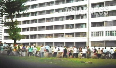 Apartment buildings in Rakrang, the south-west district of Pyongyang. In the narrow street next to the apartment people gather around to buy and sell various items. (Photo taken by Lee Jun, 2007, August) ASIAPRESS