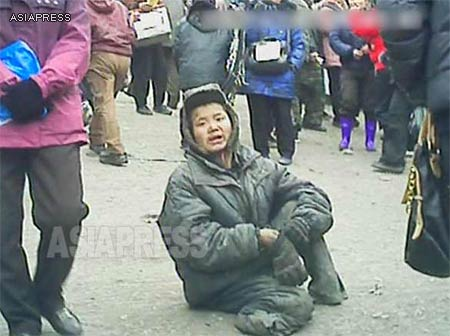 A homeless kotchebi boy sits near the entrance of the marketplace in Pyongsong, South Pyongan Province. He was begging for food and money. His legs were supposedly amputated by an accident. (March 2013)  ASIAPRESS