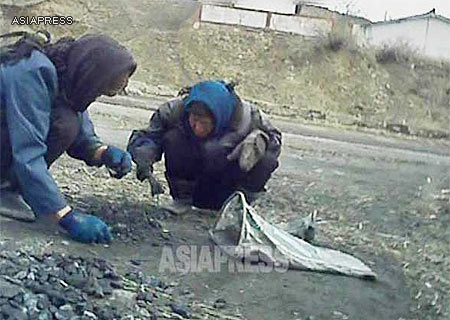 Two Women collecting coal fallen off the back of trucks. (South Pyongan Province, March 2013) ASIAPRESS