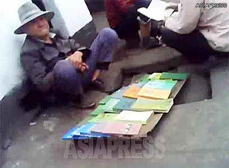 """Some textbooks sold by the roadside street-vendor: """"Secret of the mind"""", """"Exercise book (Q&A) on cerebral thrombosis"""", """"Some ideas for teaching singing and dancing"""", and """"Economic contracts"""" can be seen in this picture. (Taken in a northern border town of North Korea.) ASIAPRESS"""