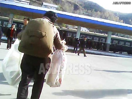 A woman with a backpack hurries to catch the train. She runs towards the station while humping a pack bursting at the seams, and bags in each of her hands. (Taken in a northern border city of North Korea. October. 2013) ASIAPRESS
