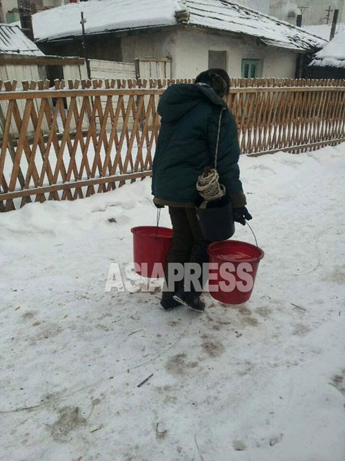 A woman returns home after fetching water from the village's public well. 2015, January. North Korean central region. (Team Mindeulle ASIAPRESS)