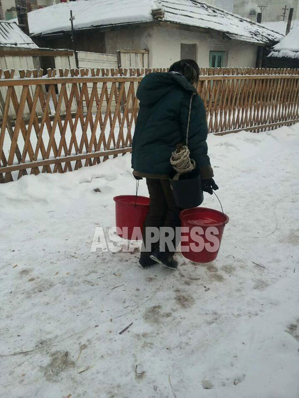 A woman is heading for her home with buckets of water from the public well. The biggest challenge is to secure water for living during winter in North Korea.  The river is frozen and there is no running water as the motor pump does not work because of insufficient power supply.  Residents collect money together to dig a well or break ice on river to draw water. (Taken by Mindulle/January 2015/ ASIAPRESS)