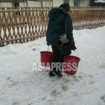 Complaints from the people are getting bigger as the supply of power and running water are worsening. A woman is going back home with buckets of water from the village pump in the midlands of North Korea on January 2015. (Taken by Mindulle, Asia Press)